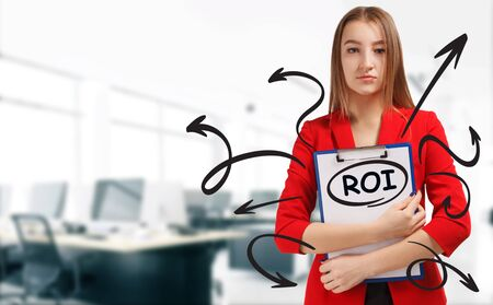 Business, technology, internet and network concept. Young businessman shows a keyword: ROI Reklamní fotografie