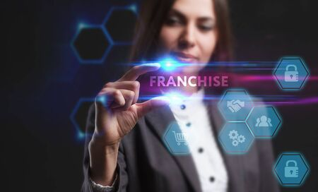 Business, Technology, Internet and network concept. Young businesswoman working on a virtual screen of the future and sees the inscription: franchise