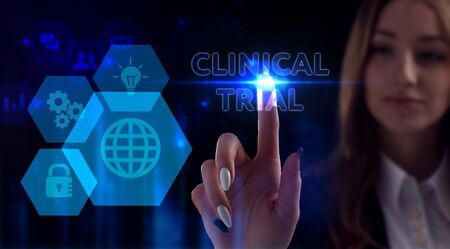 Business, Technology, Internet and network concept. Young businesswoman working on a virtual screen of the future and sees the inscription: Clinical trial Фото со стока