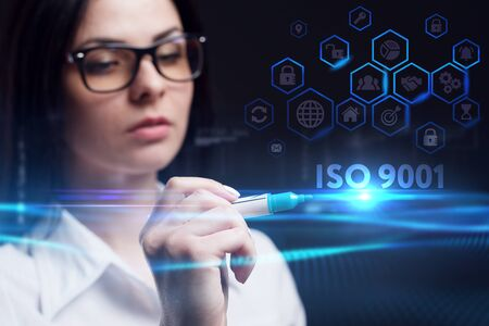 Business, Technology, Internet and network concept. Young businesswoman working on a virtual screen of the future and sees the inscription: ISO 9001 Stock fotó