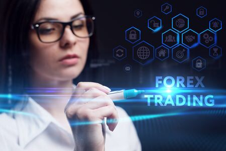 Business, Technology, Internet and network concept. Young businesswoman working on a virtual screen of the future and sees the inscription: Forex trading
