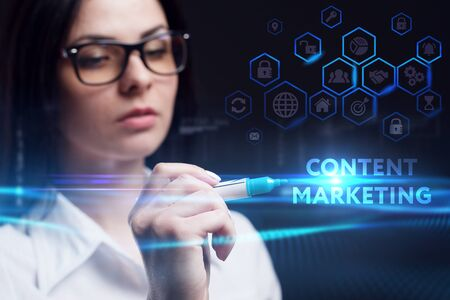 Business, Technology, Internet and network concept. Young businesswoman working on a virtual screen of the future and sees the inscription: Content marketing