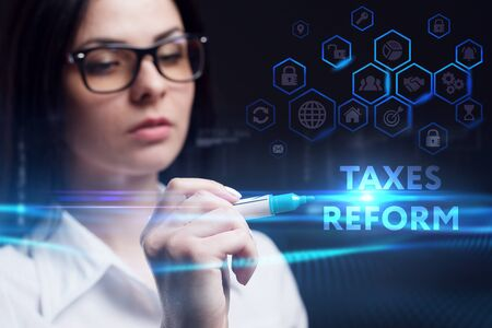 Business, Technology, Internet and network concept. Young businesswoman working on a virtual screen of the future and sees the inscription: Taxes reform