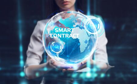 Business, Technology, Internet and network concept. Young businessman working on a virtual screen of the future and sees the inscription: Smart contract Фото со стока