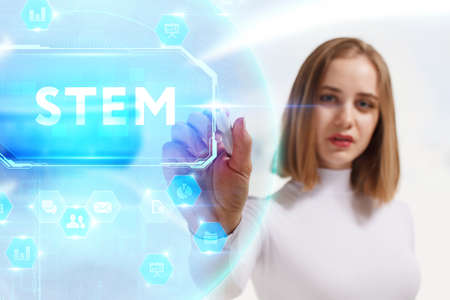 Business, Technology, Internet and network concept. Young businesswoman working on a virtual screen of the future and sees the inscription: STEM