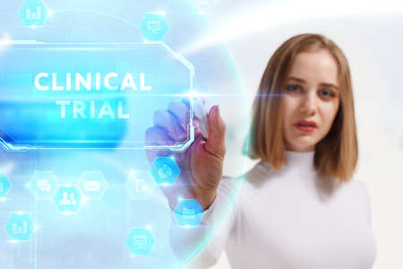 Business, Technology, Internet and network concept. Young businesswoman working on a virtual screen of the future and sees the inscription: Clinical trial 스톡 콘텐츠