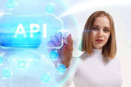 Business, Technology, Internet and network concept. Young businesswoman working on a virtual screen of the future and sees the inscription: API 스톡 콘텐츠