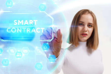 Business, Technology, Internet and network concept. Young businesswoman working on a virtual screen of the future and sees the inscription: Smart contract 스톡 콘텐츠