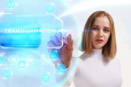 Business, Technology, Internet and network concept. Young businesswoman working on a virtual screen of the future and sees the inscription: Transformation