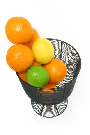 fruit drop: Citrus fruit drop into a wire basket over white Stock Photo