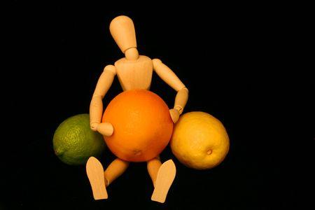 Wooden Manikin with citrus fruit photo