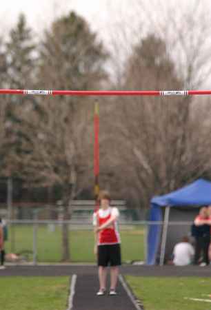 grasp: young man ready to pole vault (focus on the bar in foreground)