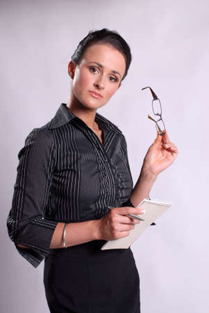 Young business woman holding glasses, pad and pen Stock Photo