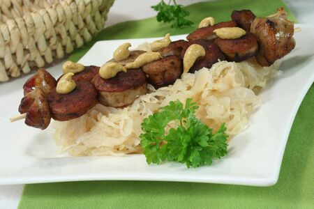 kohl: Sauerkraut on a plate, with a sausage on a skewer daruf mustard