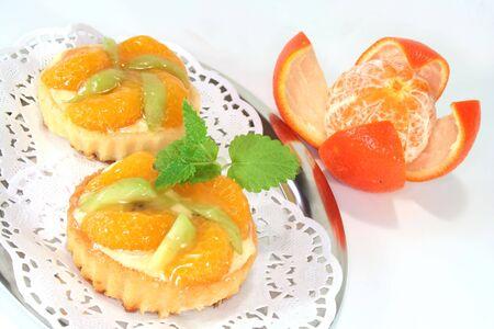 confiserie: Mandarin tartlet with lemon balm on a silver platter