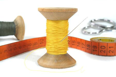 presumptuous: old bobbin with needle, measuring tape and Schrere on a white background