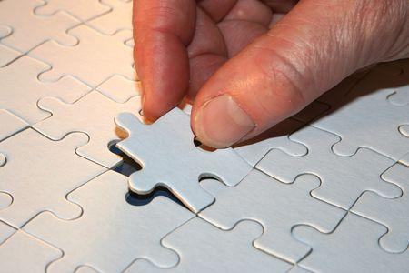 Hand mit Teil des Puzzles zu Puzzlespiel