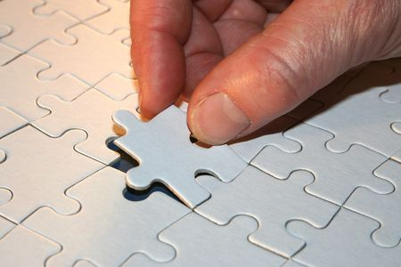 outsiders: Hand with part of the jigsaw to puzzle Stock Photo