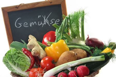 illiterate: Colorful mix of many different fresh vegetables in a basket with a board