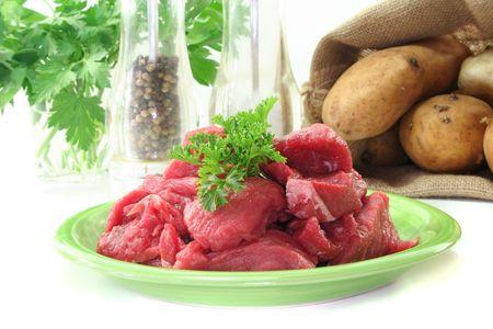 slaughtering: stufato di crudo fresco con un mazzetto di prezzemolo su una piastra di