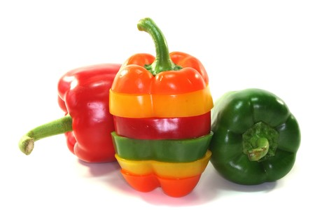 different colored peppers stacked on a white background