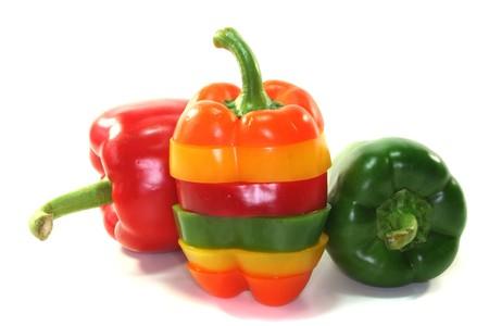 verschiedenen farbigen Paprika gestapelt auf einem weißen Hintergrund Lizenzfreie Bilder