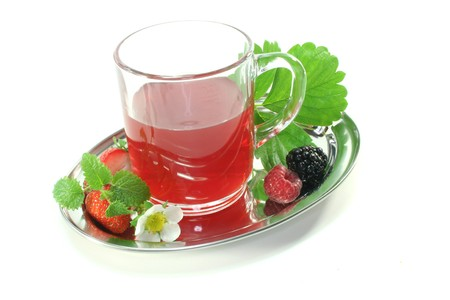 a glass of forest fruit tea with fresh fruit