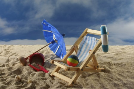 Deck chair with sun umbrella, water polo and swimming ring on the beach Stock Photo - 7227396