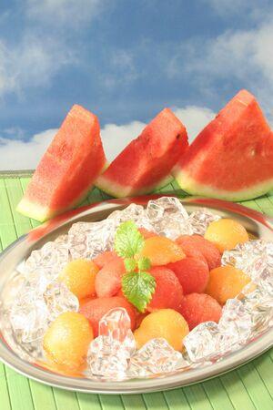 pancetta cubetti: palline di melone colorato su cubetti di ghiaccio e Melissa  Archivio Fotografico