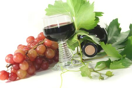 a glass of red wine with bottle, grapes and leaves Stock Photo - 7434916
