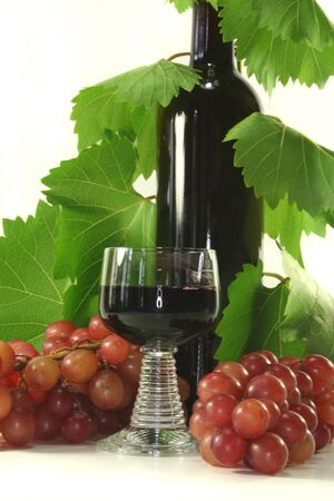 a glass of red wine with bottle, grapes and leaves Stock Photo - 7434921