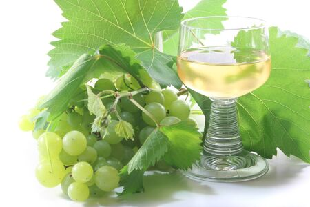 a glass of white wine with grapes and leaves Stock Photo - 7434920