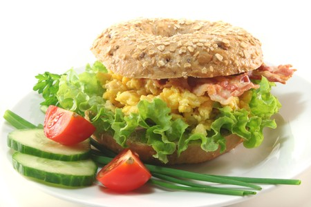 Rye bagel with salad, scrambled eggs and bacon photo
