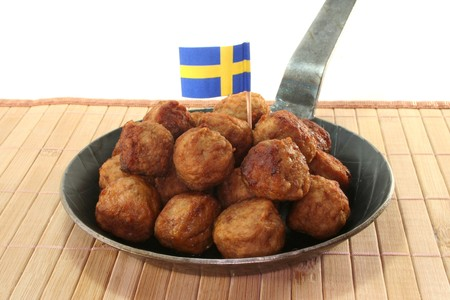 the swedish flag: Koettbullar in a pan with Swedish flag Stock Photo