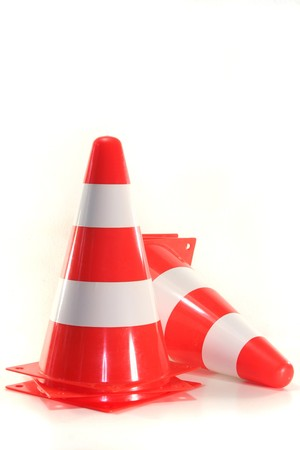 redirect: red and white construction pylons before a white background