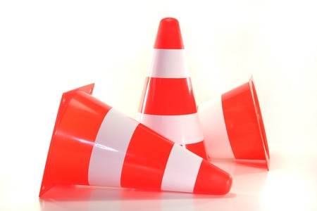 redirect: three red and white construction pylons before a white background Stock Photo