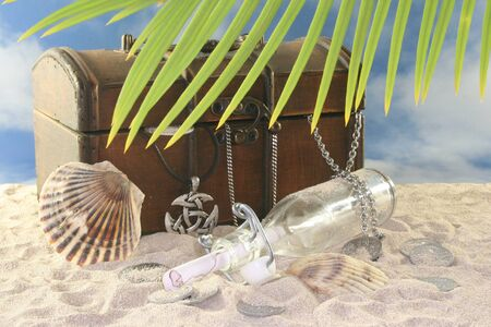 Bottle post with old coins, old chest in the sand and shell photo
