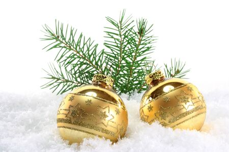 one golden Christmas ball with pine branches lies in the snow photo