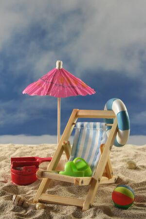 Deck chair with umbrella, water polo and swimming ring on the beach Stock Photo - 8166693