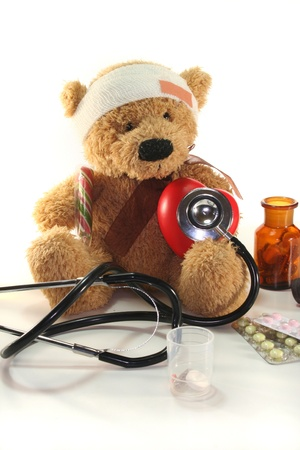 injured Teddy child with doll doctor on a white background