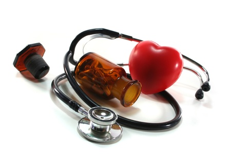 Stethoscope with heart and pills on a white background photo