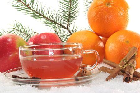 Winter Tee mit frischen Äpfeln und Orangen, Pine Zweig und Gewürze im Schnee Lizenzfreie Bilder