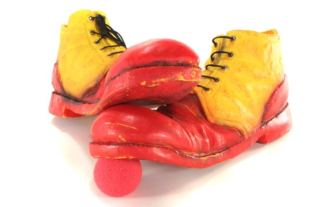 red and yellow clown shoes stand on a red clown nose