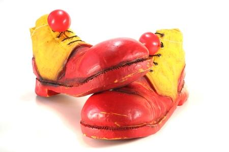 payaso: zapatos de payaso de rojo y amarillo con nariz de payaso rojo sobre fondo blanco
