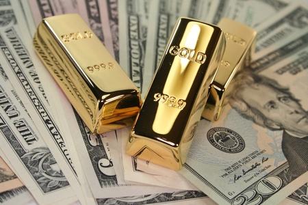 bullion: three large gold bars on many dollar bills