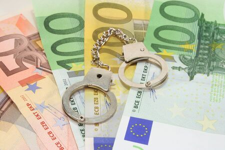 receptive: silver handcuffs on many large euro notes