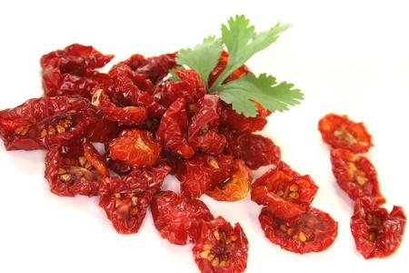 legumbres secas: frescos tomates secos con una hoja de cilantro sobre fondo blanco Foto de archivo