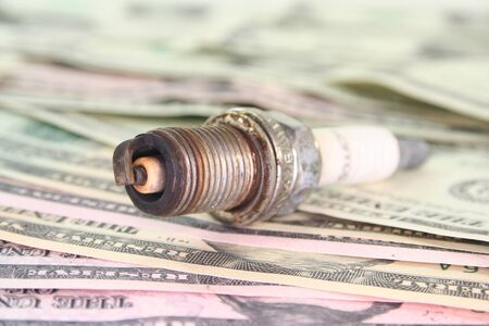 old rusty spark plug on many dollar bills Stock Photo - 8999880