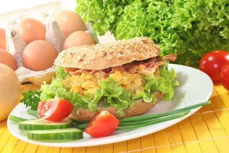 scrambled eggs: Bagel centeno con ensalada, revuelto y bacon