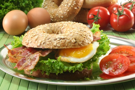 bagel: Rye bagel with salad, fried egg and bacon Stock Photo